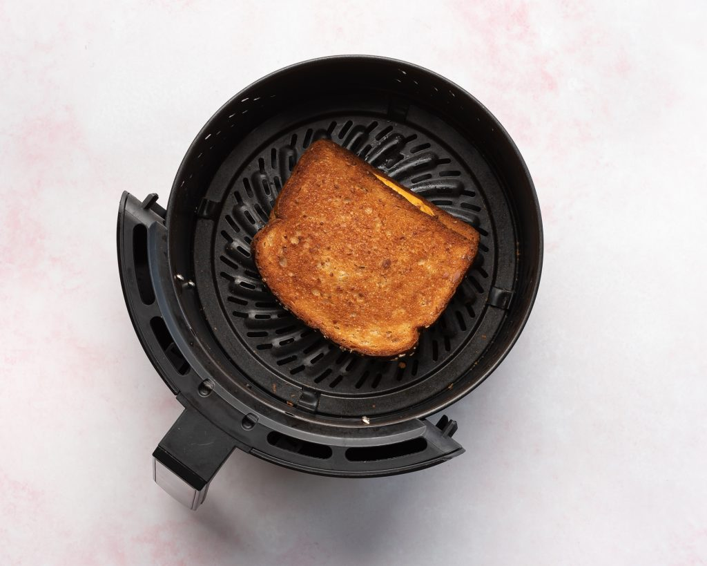 air fryer with a browned grilled cheese sandwich in it