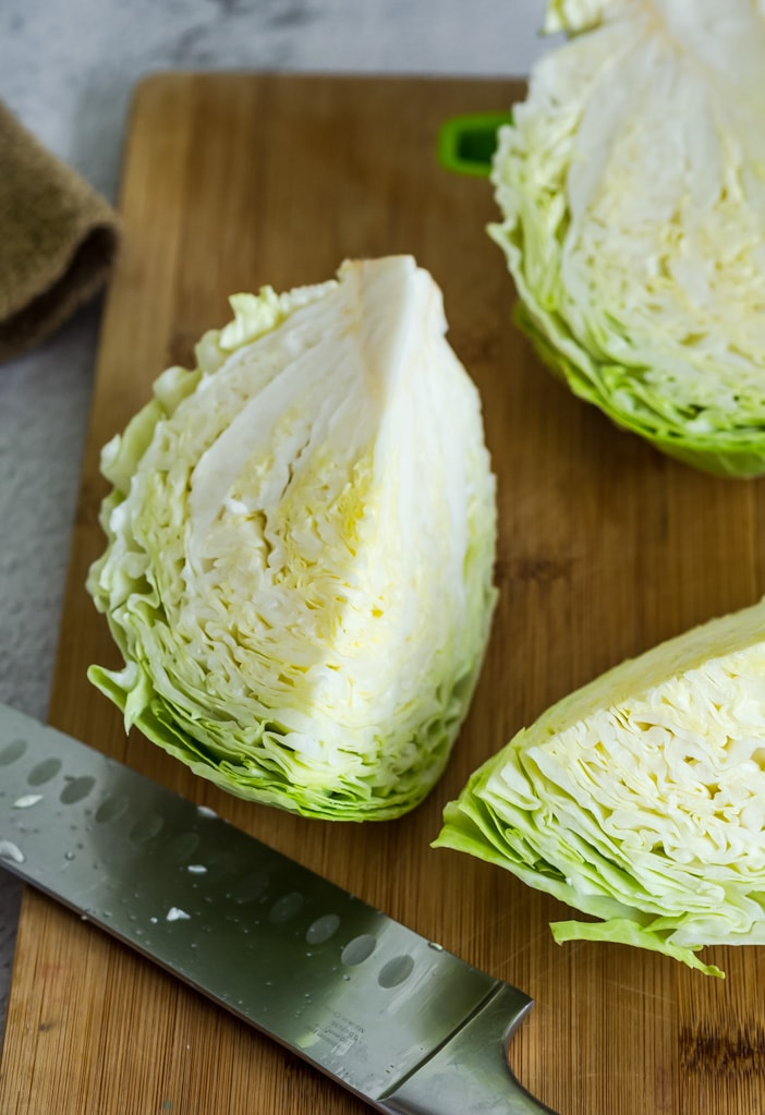 cut green cabbage pieces on a wooden cutting board