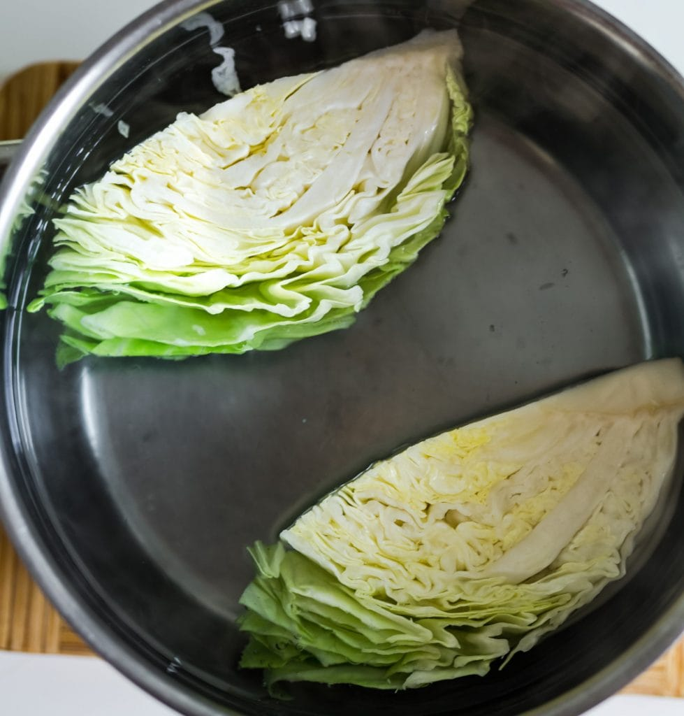 boling quarters of green cabbage in a large pot of water