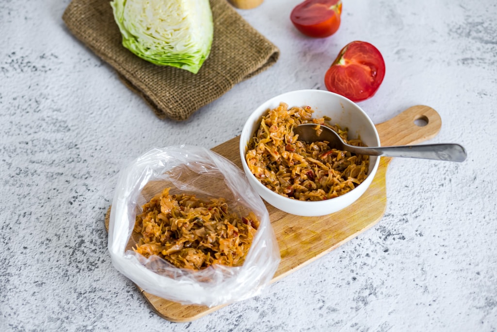 placing cooked cabbage in a freezer-safe bag