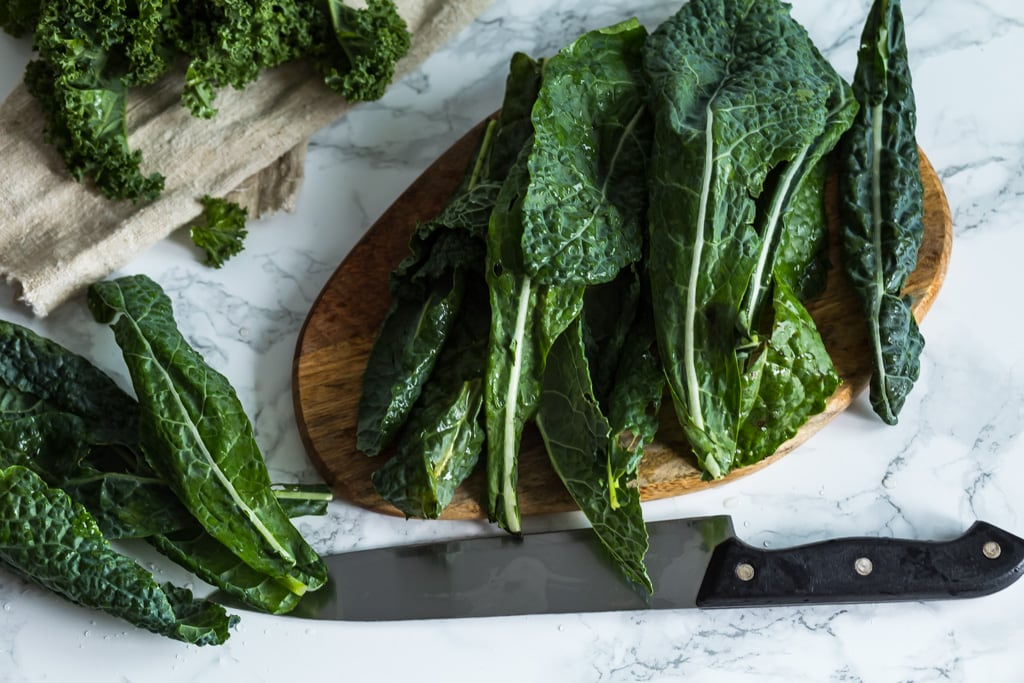 whole kale leaves on a wooden cutting board