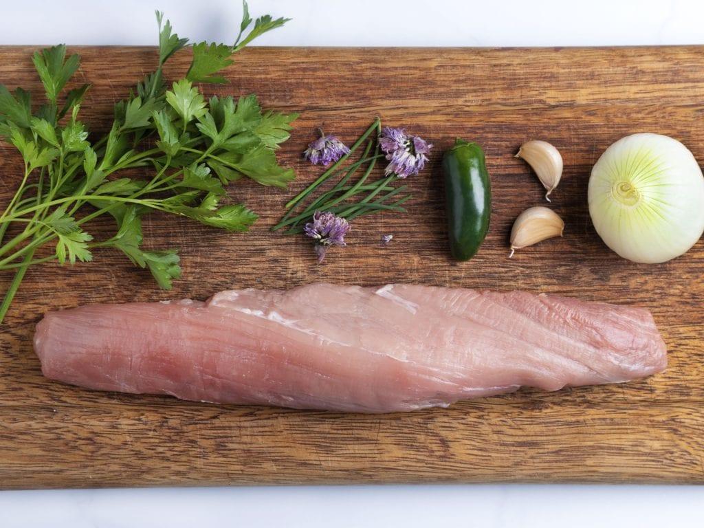 Ingredients on a cutting board: raw pork tenderloin, jalapeno pepper, fresh herbs and garlic