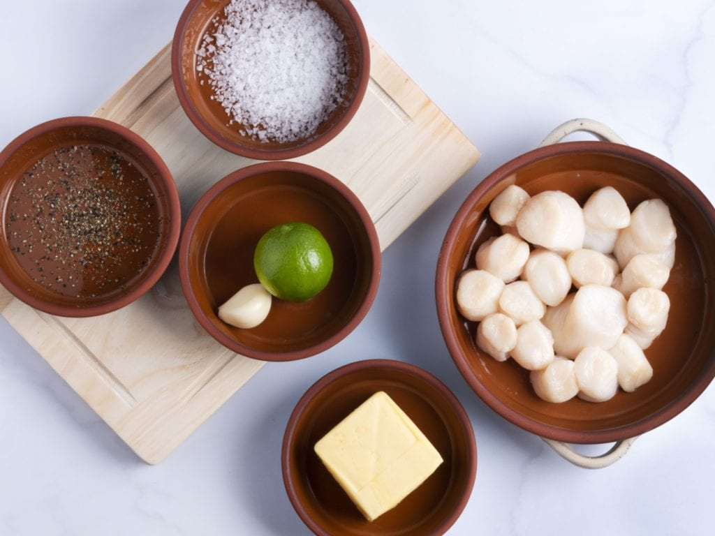 ingredients in bowls: raw scallops, lime, butter, salt and pepper