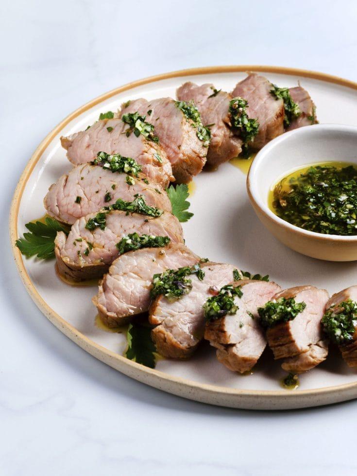 sous vide pork tenderloin sliced on a white platter with green herb sauce