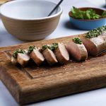 sous vide pork tenderloin sliced on a wooden cutting board with green herb sauce