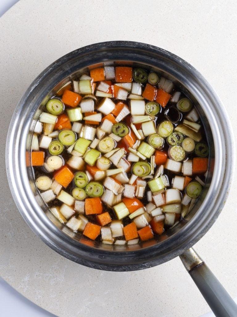 teriyaki sauce with scallions carrots an onions in a pot