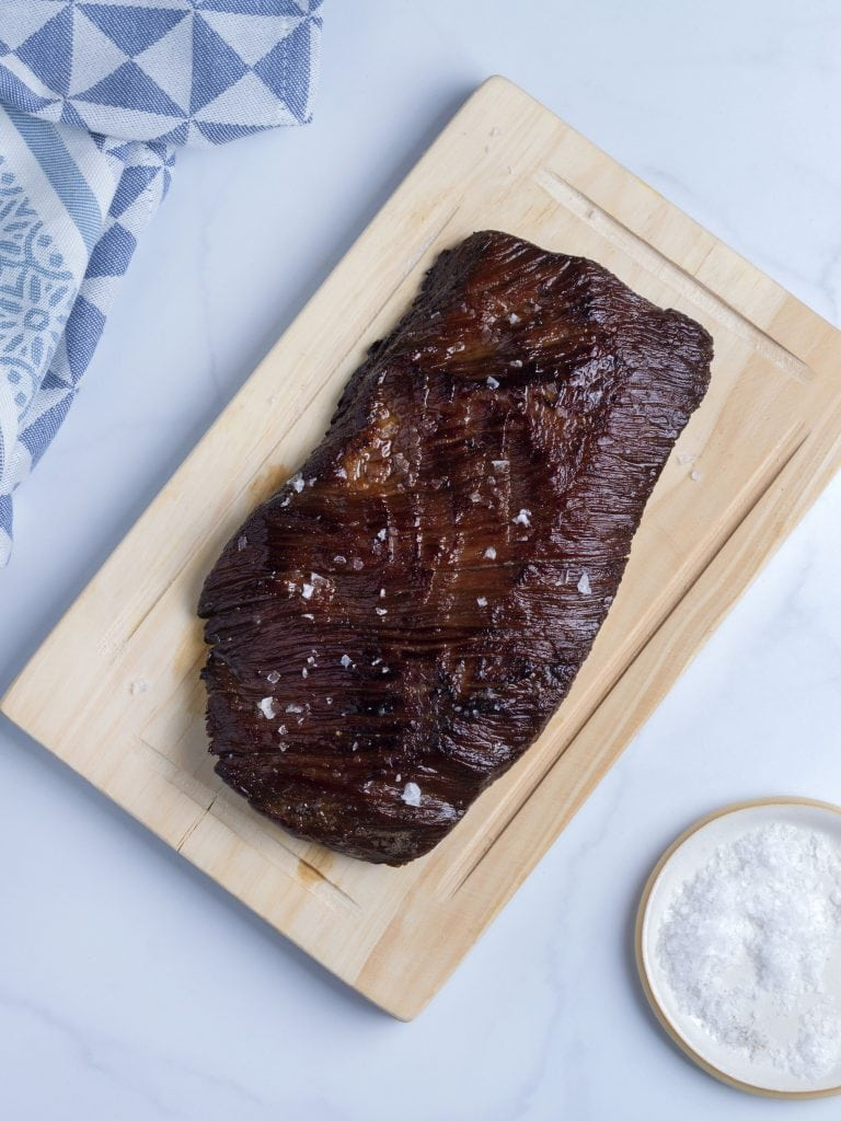 seared flank steak on a wooden cutting board