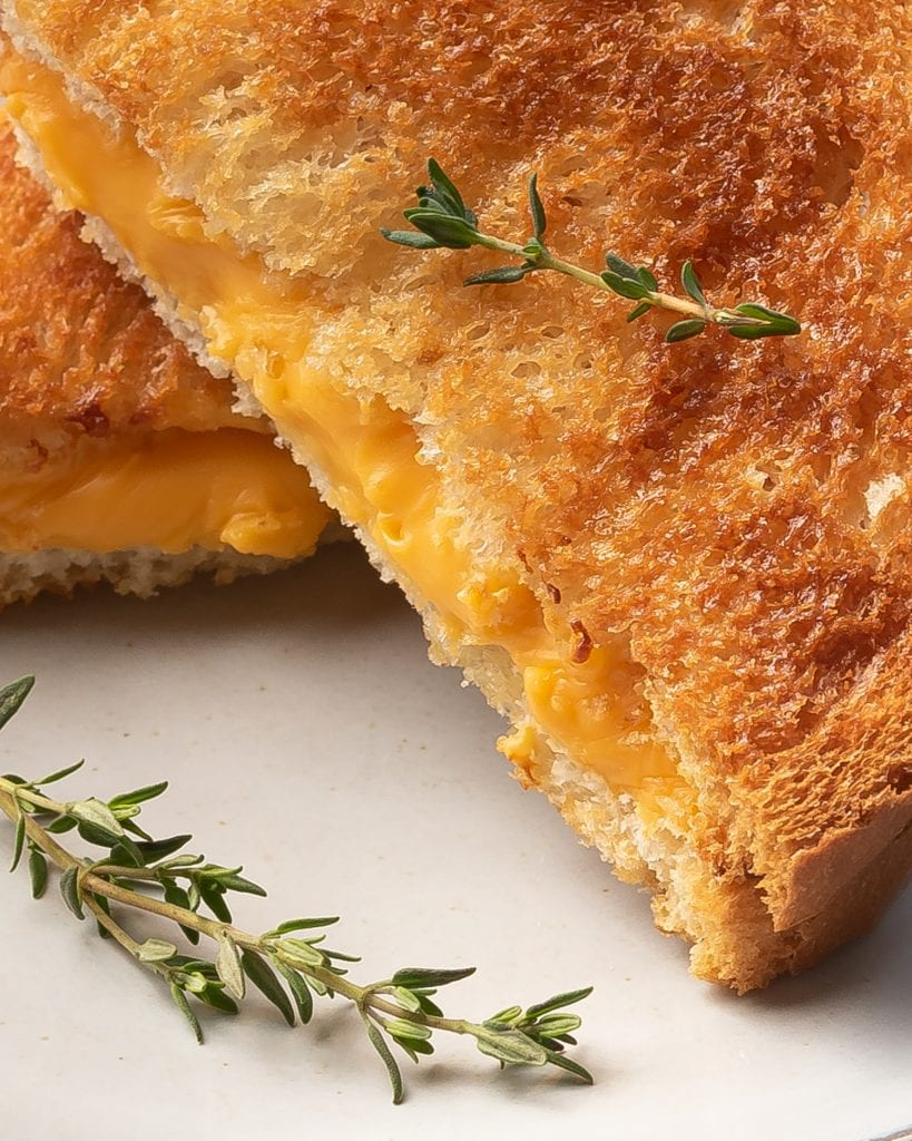 close up on a grilled cheese sandwich with fresh thyme