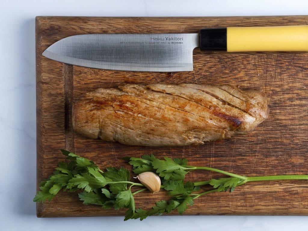 seared pork tenderloin on a wooden cutting board with fresh herbs