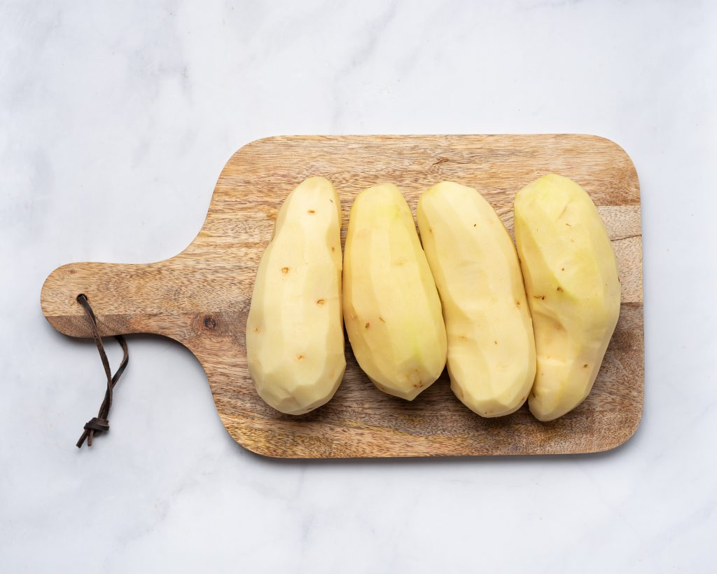four large russet potatoes peeled on a wooden cutting board