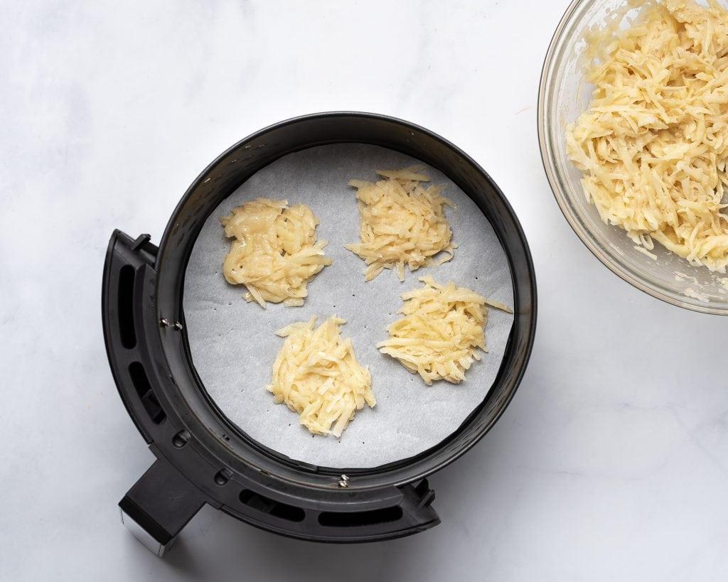 hash brown patties in an air fryer basket before cooking
