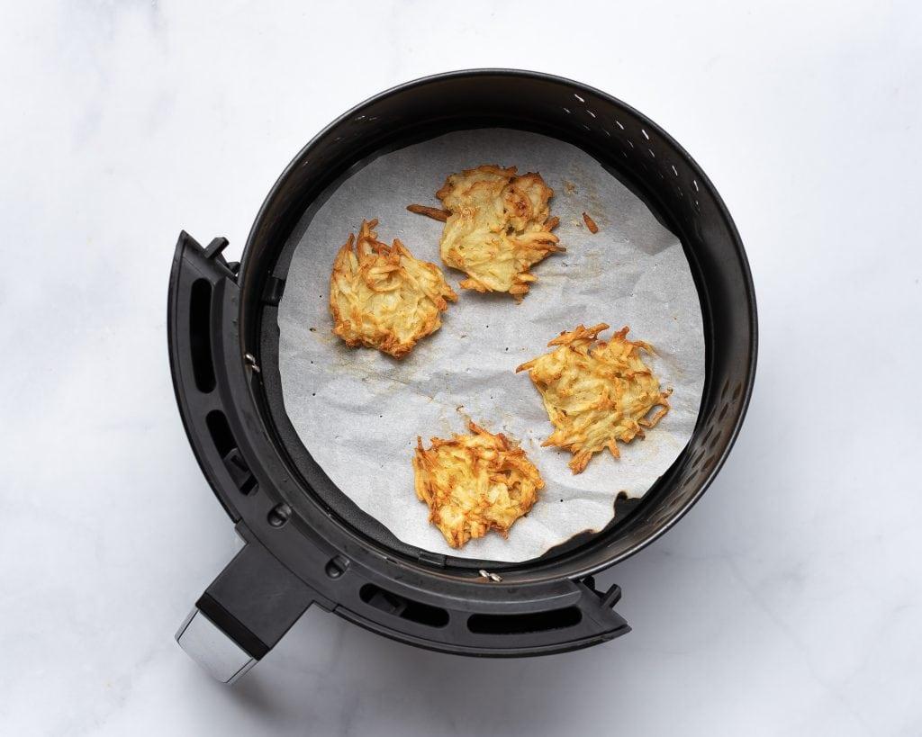 crispy potaoto patties in an air fryer basket