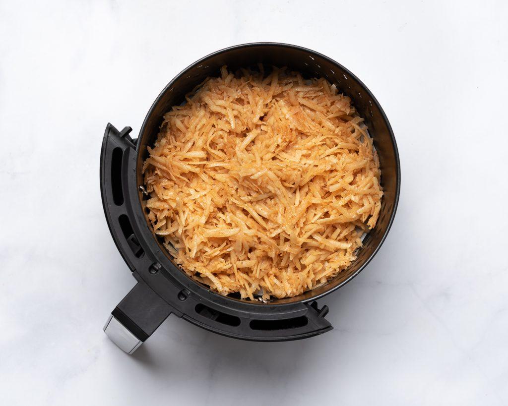 hash browns in an air fryer basket