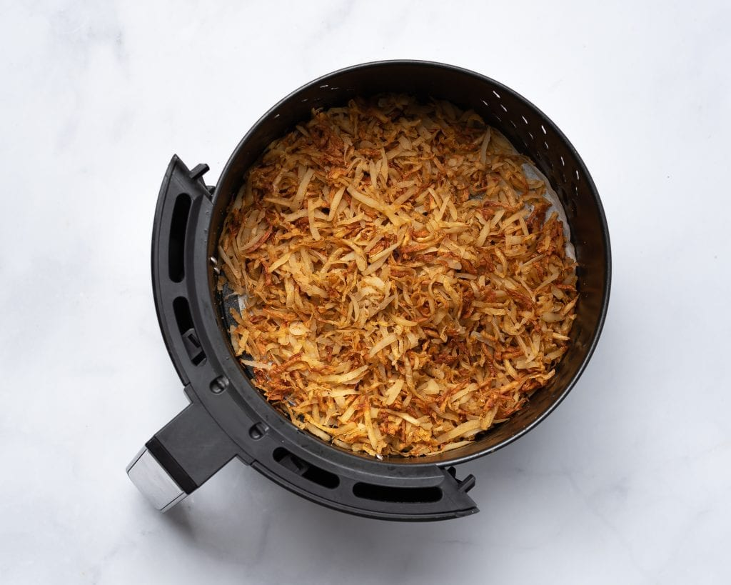 cooked hash browns in an air fryer basket
