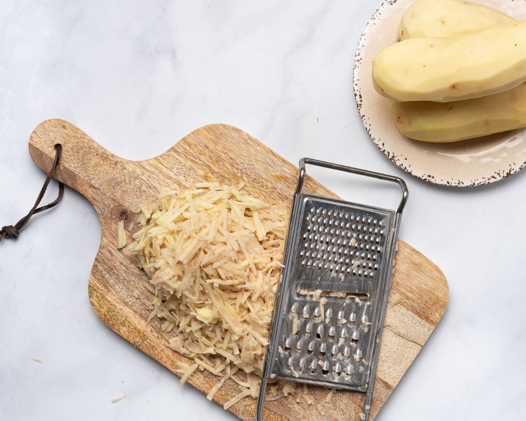 grating russet potatoes on a wooden cutting board
