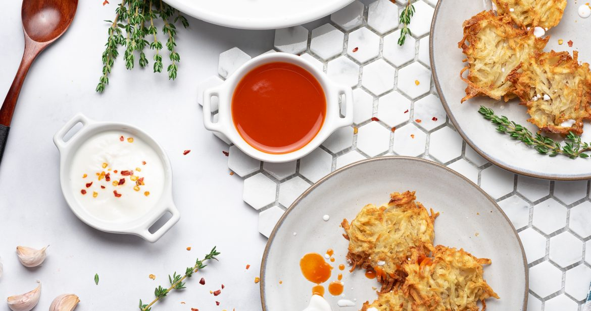 air fryer hash browns on a white round dinner plate with hot sauce