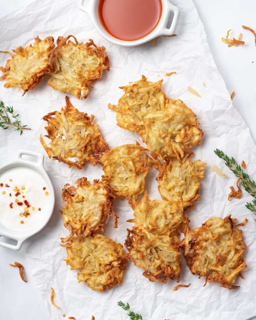 hash brown patties on a white background with fresh herbs and ranch sauce