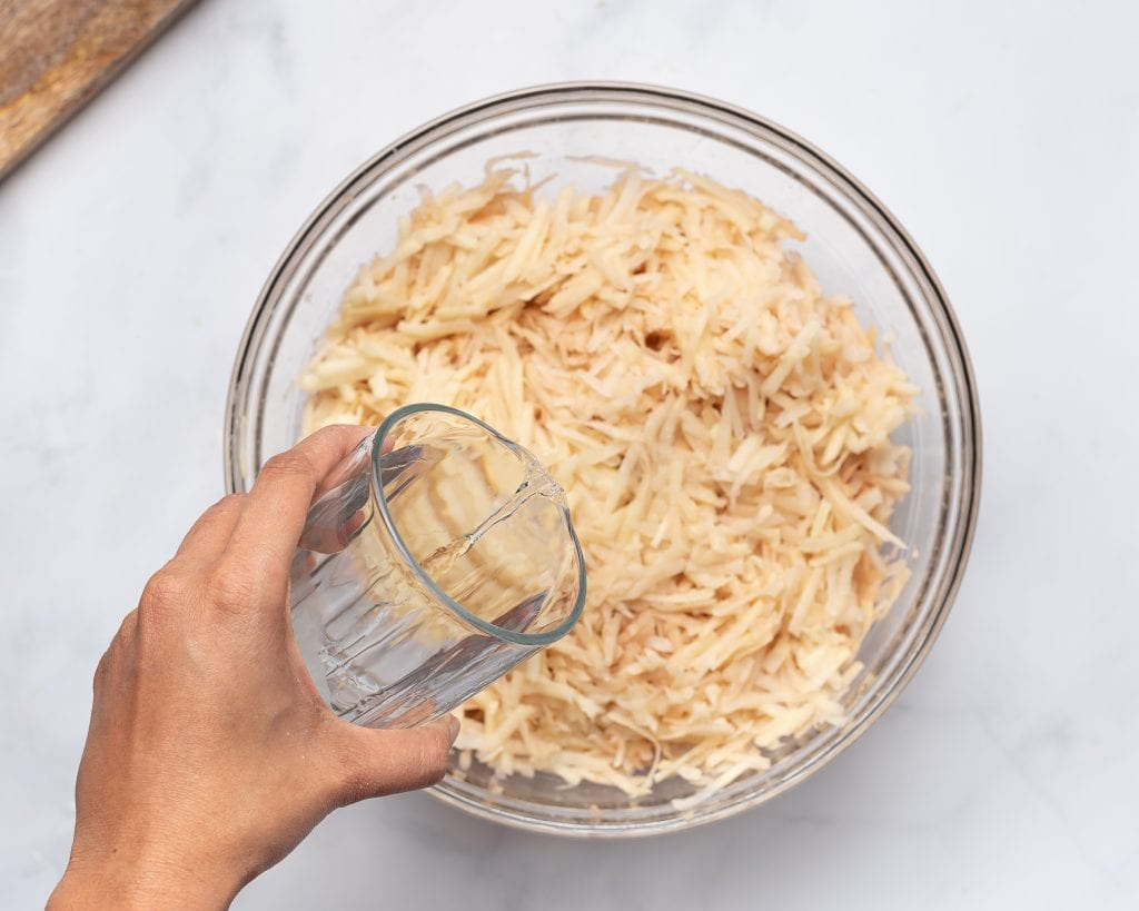 covering grated potaotes in water to soak
