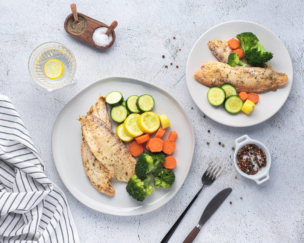 Instant pot tilapia with vegetables on whtie dinner plates with salt and pepper