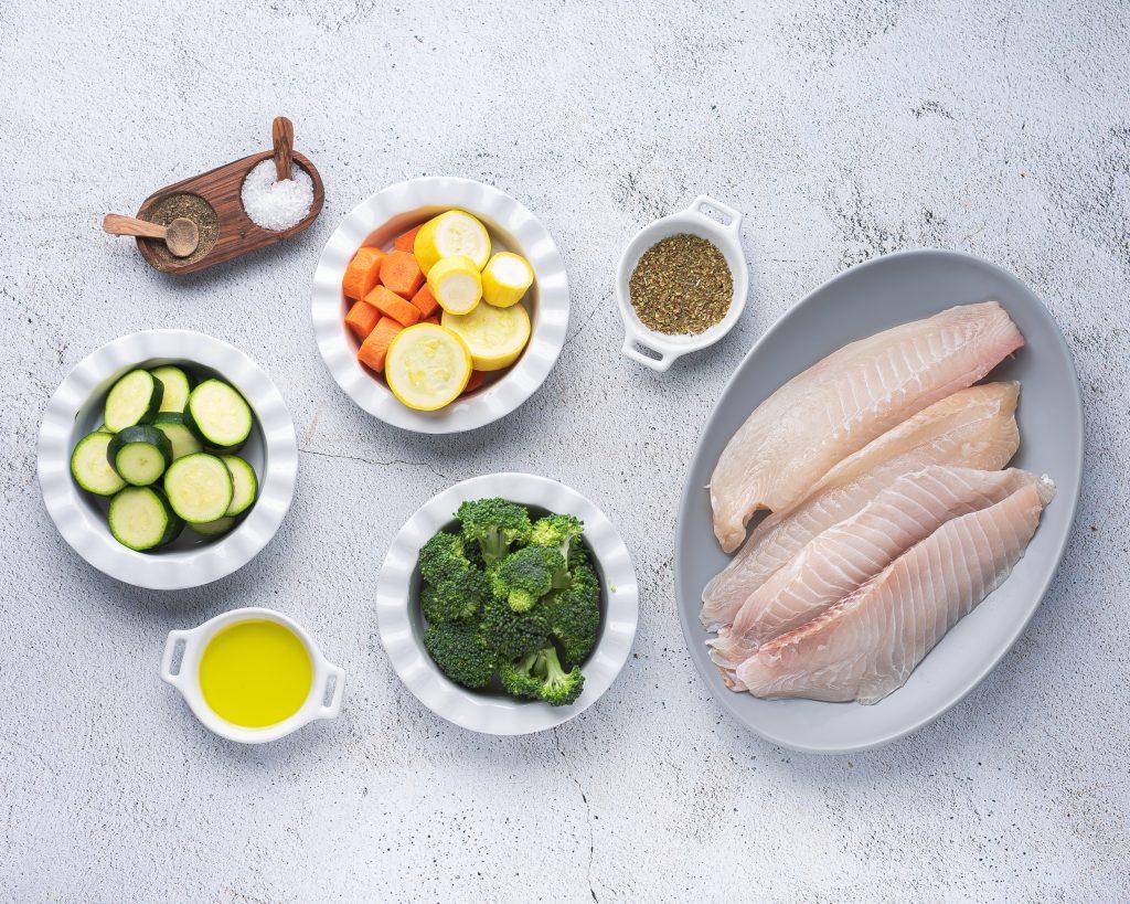 ingredients for instant pot fish: tilapia, chopped vegetables, olive oil, salt and pepper
