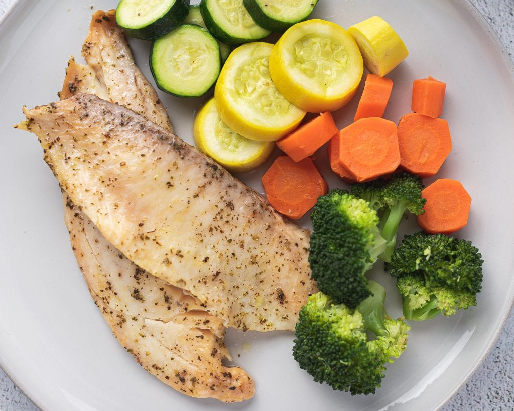 white plate with instant pot tilapia, broccoli, carrots and squash